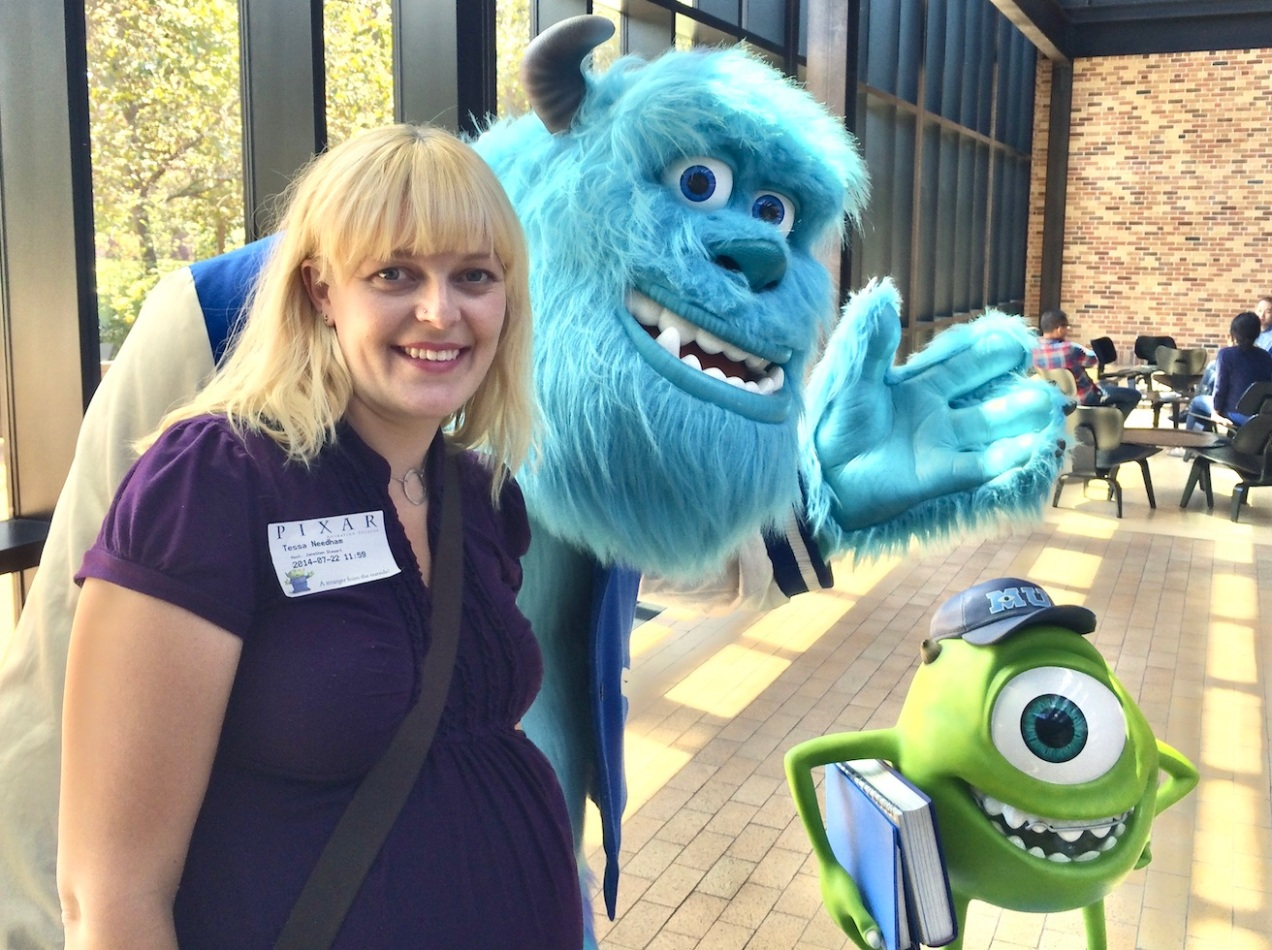 Tess standing with statues of Mike and Sully from Monsters University